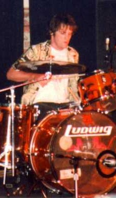 Frank plays the transparent orange drums.